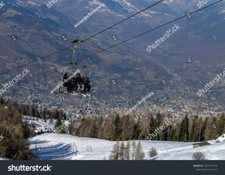 stock-photo-pila-aosta-italy-feb-four-middle-aged-men-skiers-take-a-chair-lift-up-the-mountain-at-1031277199