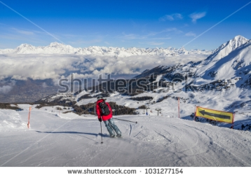 stock-photo-pila-aosta-italy-feb-one-skier-in-jeans-going-downhill-a-piste-with-panoramic-view-of-1031277154