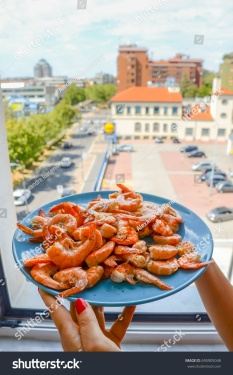 stock-photo-plate-of-shrimps-prawns-with-a-city-background-695905048