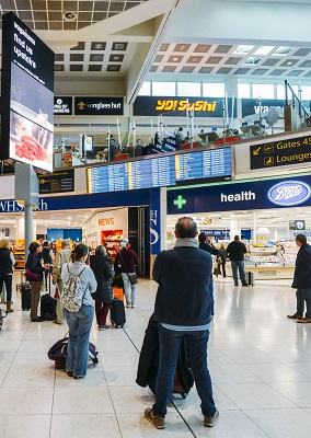 London Gatwick, March 15th, 2018: Passengers check their flight information on a digital display at London Gatwick's North Terminal. Various options to shop and eat while passengers wait