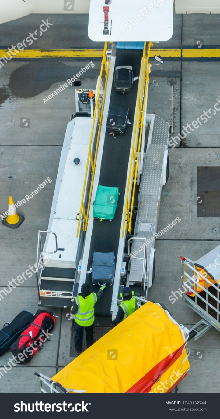 stock-photo-high-perspective-of-unidentifitable-baggage-handlers-picking-up-suitcases-from-a-conveyor-belt-1048132744