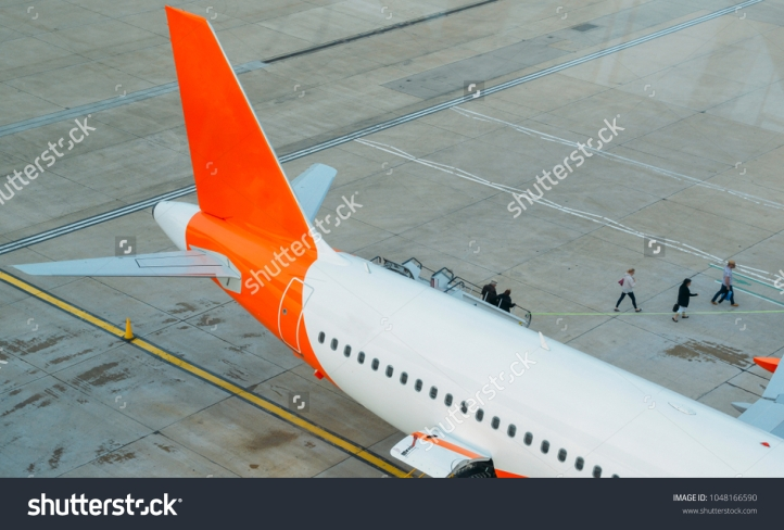 stock-photo-passengers-disembark-from-an-airplane-and-walk-on-tarmac-towards-the-terminal-building-1048166590