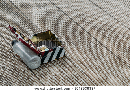 stock-photo-stripped-change-box-on-ground-supported-open-by-a-water-bottle-asking-for-donations-from-out-of-1043530387