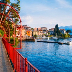 Red garden arch on coastline leading towards the beautiful and historic city of Varenna on the edge of Lake Como in the northern Italian region of Lombardy.