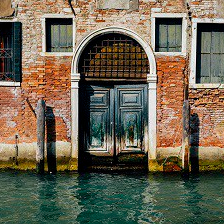 Facade of partially mossy old brick house with wooden vintage door on narrow canal in Venice, Italy.