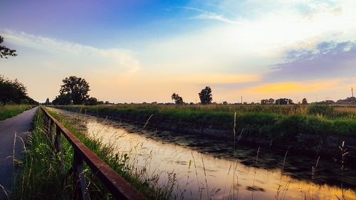 Empty cycling path along the Naviglio Pavese, canal at sunset. The canal stretches for 30km from Pavia to Milan in Lombardy, northern Italy.