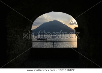stock-photo-shooting-through-a-window-sill-towards-sunset-at-lake-como-italy-1081356122