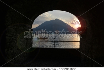 stock-photo-shooting-through-a-window-sill-towards-sunset-at-lake-como-italy-1082001680