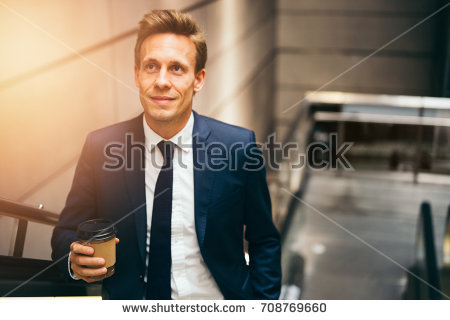 stock-photo-smiling-young-executive-in-a-suit-drinking-a-coffee-and-riding-up-an-escalator-in-a-subway-station-708769660