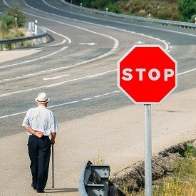 Elderly man walking with a cane past a red stop sign leading to a curving highway - conceptual image