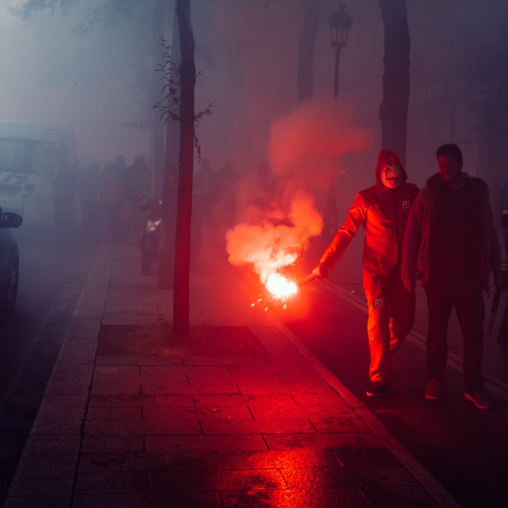 Protestors wearing a Guy Fawkes mask light gas canisters to express their anger against French President Macro's government, among other issues, on the streets of Paris