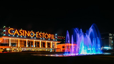 Facade of the Casino Estoril with colourful fountain show at night. Casino Estoril is one of the largest casinos in Europe and inspiration for Ian Fleming's Casino Royale