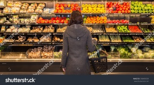 stock-photo-woman-standing-in-front-of-a-row-of-produce-in-a-grocery-store-358499339