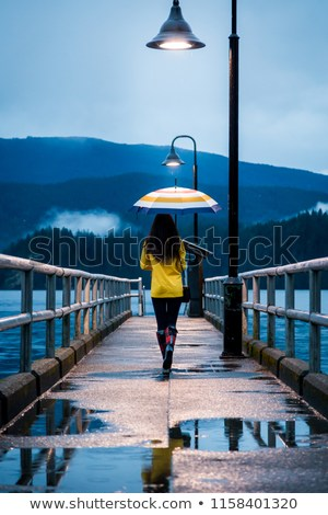 young-woman-yellow-raincoat-standing-450w-1158401320