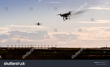 stock-photo-a-silhouette-of-a-drone-rapidly-moving-towards-an-departing-aircraft-near-a-airport-1264805419