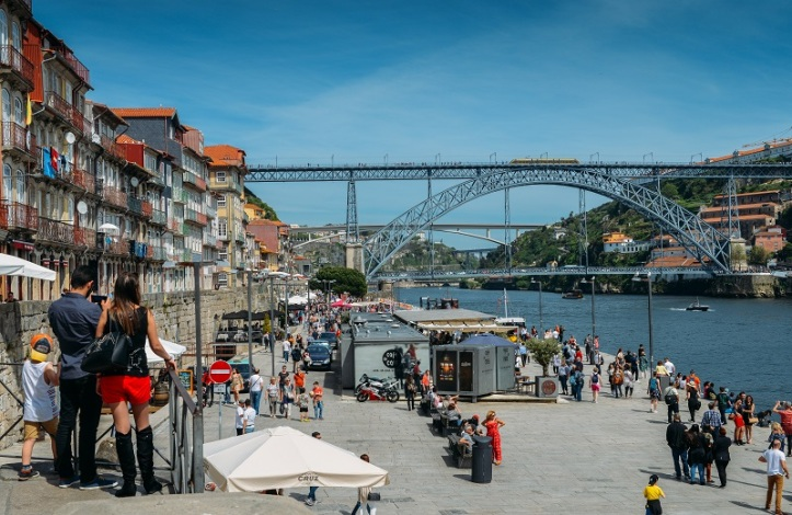 Couple at Ribeira docks facing Dom Luis I Bridge over Douro River and Gaia town, Porto, Portugal