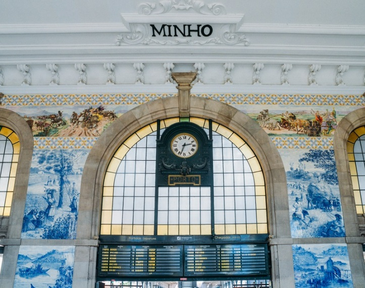 Clock of the historical Sao Bento train station in Porto, Portugal. Wall is covered in blue azulejo tiles