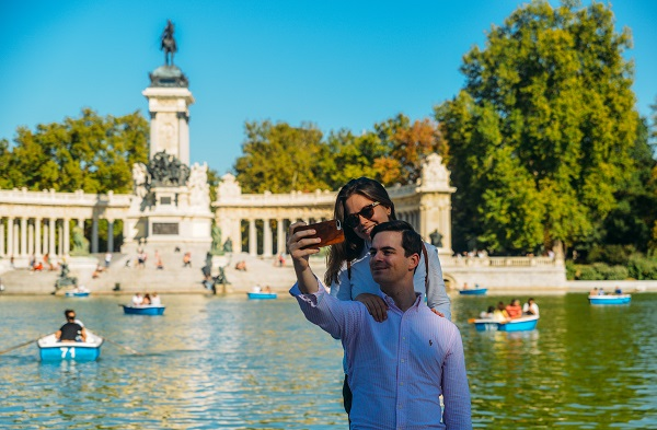 Couple takes a selfie in front of boats across from monument to Alfonso XII in the Parque del Buen Retiro, Madrid, Spain
