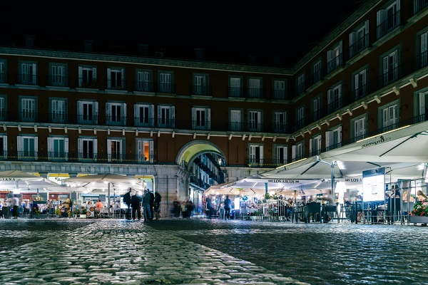People walking and sitting at restaurant terraces at Plaza Mayor Madrid, Spain at night