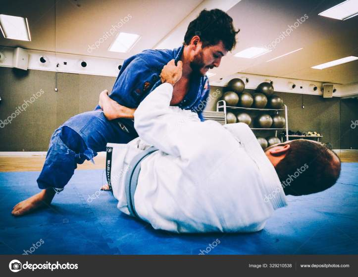 Two young men practice Brazilian Jiu-Jitsu sparring, a grappling type martial arts with a kimono gi - NOT STAGED CONTENT OR AT CLOSED EVENT