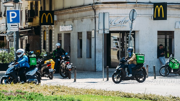 Glovo and UberEats delivery couriers on motorbike in front of a McDonalds restaurant during the Coronavirus Covid-19 outbreak