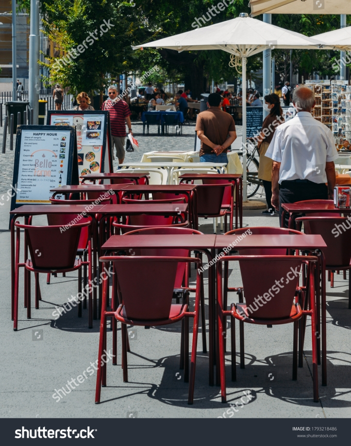stock-photo-lisbon-portugal-august-waiters-standing-in-front-of-empty-restaurant-terraces-waiting-1793218486